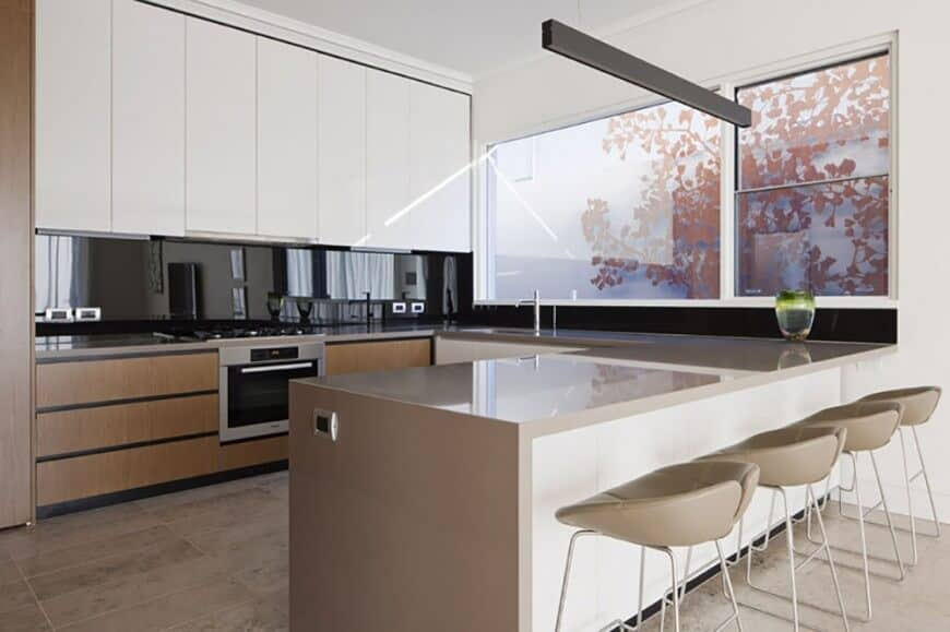 Modern kitchen with smooth gray breakfast bar counter paired with modern seats.
