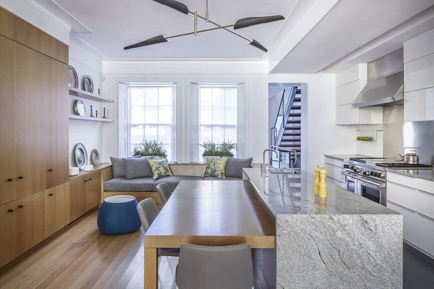 A small great room featuring a cozy couch on the side and a breakfast bar counter connected to the stylish marble waterfall-style center island.