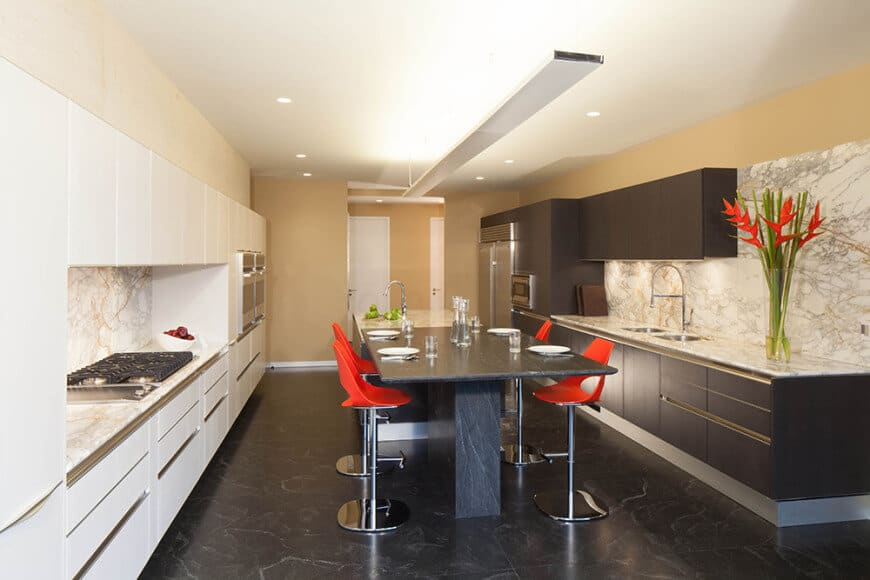 This kitchen boasts stylish marble tiles flooring and marble kitchen backsplash that look fancy. The area offers a center island with a breakfast bar counter on its side.