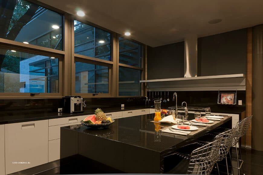 This modern kitchen boasts black countertops on both kitchen counters and the island. The area has dark finished flooring and glass windows.