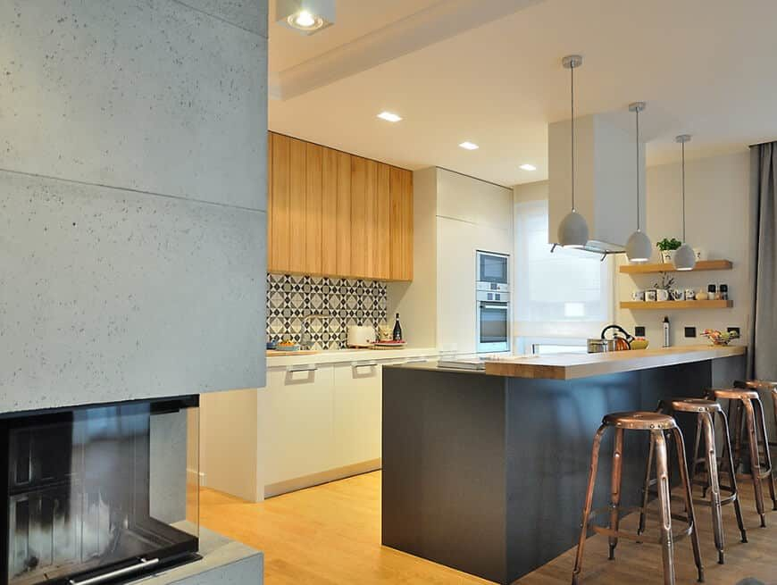 A small kitchen featuring a breakfast bar counter lighted by pendant lights. There are built-in shelving on the side as well.