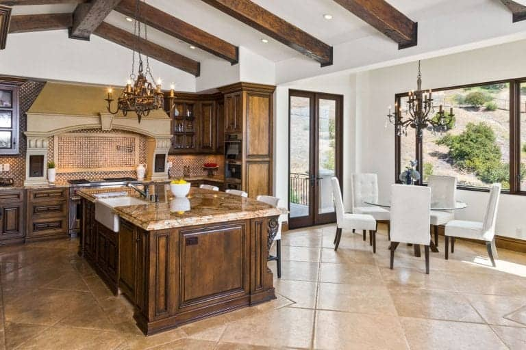 A large kitchen area with brown tiles flooring and a vaulted ceiling with exposed beams. The kitchen boasts a large center island with an elegant countertop, lighted by a gorgeous chandelier.