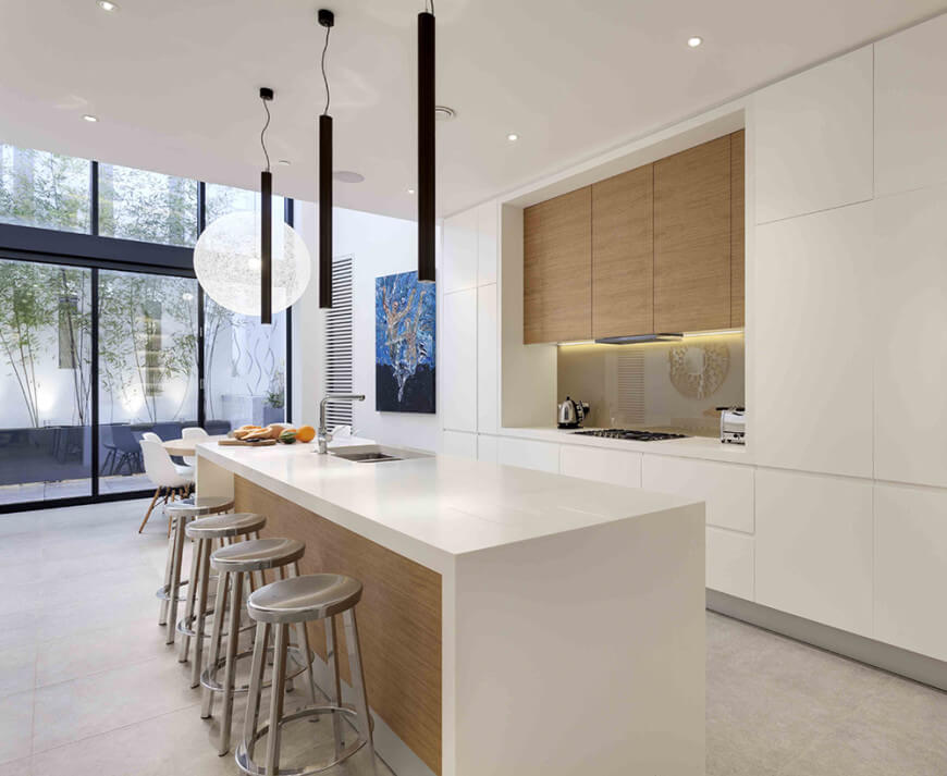 A white single wall kitchen featuring white tiles flooring and a tall ceiling. It also has a waterfall-style island with space for a breakfast bar.