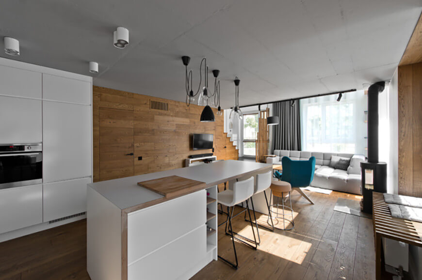A great room offering a modern living space with a cozy couch and a kitchen with a breakfast bar island.