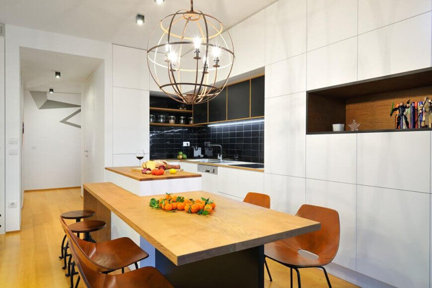 A small kitchen area featuring a small island with a wooden top breakfast bar counter lighted by enchanting ceiling light.