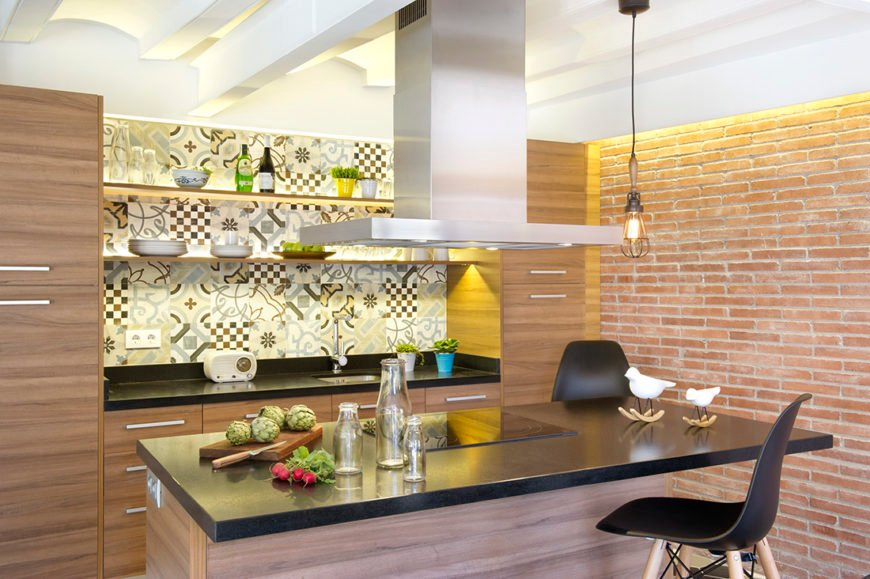 Small kitchen area with a stunning white ceiling and a brick wall. The kitchen features a black kitchen counter and a breakfast bar island with a black countertop.
