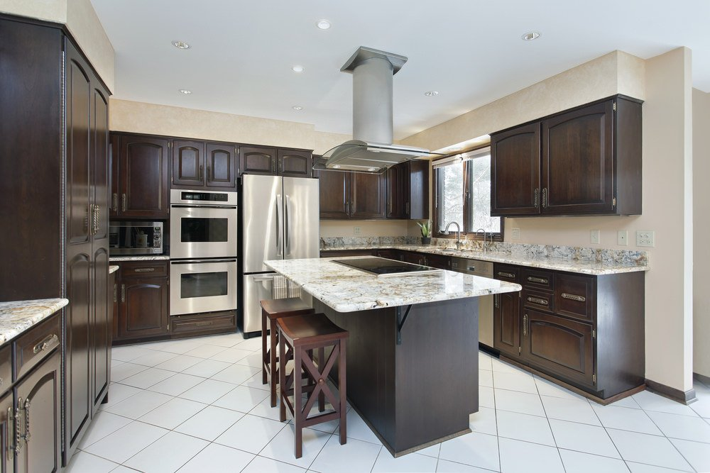 A kitchen with white tiles flooring and brown cabinetry and kitchen counters, along with marble countertops.