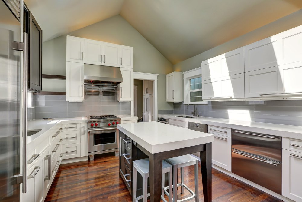 A kitchen with hardwood floors and a shed ceiling with white cabinetry and white kitchen counters. The small island features a thick white countertop.