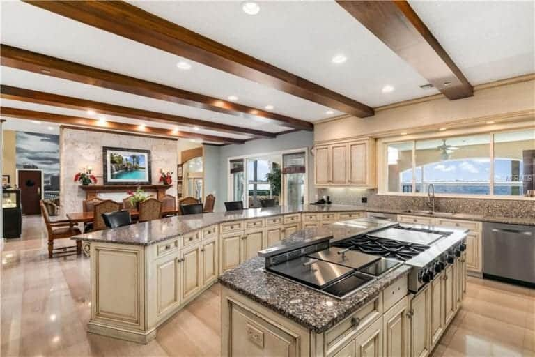 A large classy kitchen with perfectly-polished flooring and a ceiling with beams. The area also has a curved kitchen counter and a center island, both with granite countertops.