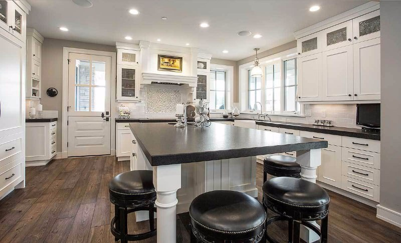 Large kitchen with hardwood floors and gray walls. It features white cabinetry and kitchen counters with black countertops.