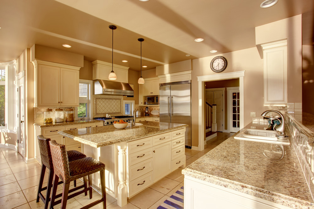 This kitchen boasts two kitchen counters and a center island, all featuring granite countertops. The area is lighted by recessed and pendant lights.