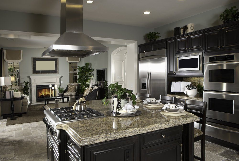 This kitchen features gray walls and tiles flooring, along with a center island with a granite countertop and has a breakfast bar.