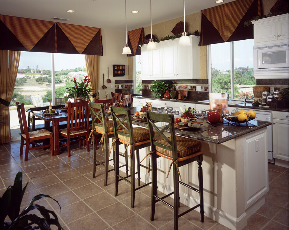 A dine-in kitchen with gray tiles flooring and granite countertops on both kitchen counter and kitchen island. It offers a dining table set and a breakfast bar.