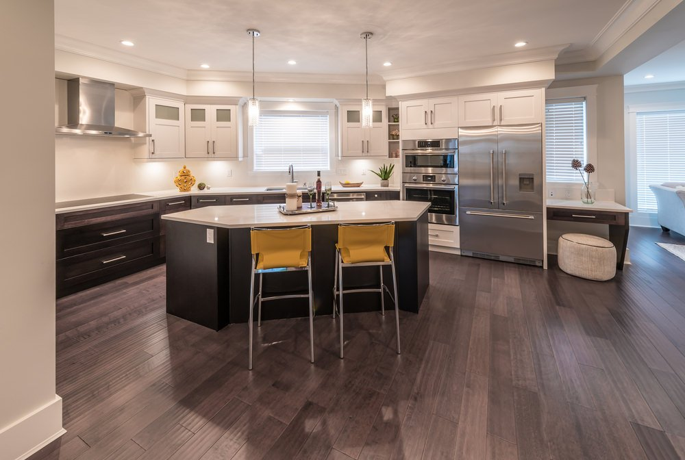 A spacious kitchen featuring white countertops on both kitchen counter and the island with a breakfast bar for two, lighted by pendant lights.