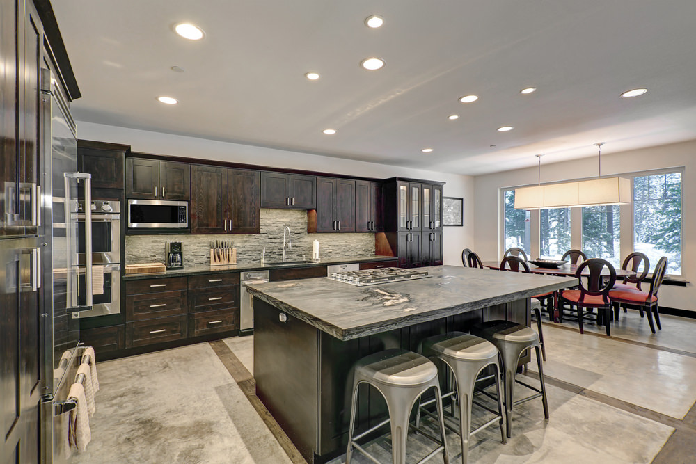 Spacious L-shaped kitchen with a gorgeous oval-shaped dining table set on the side along with a breakfast bar island.