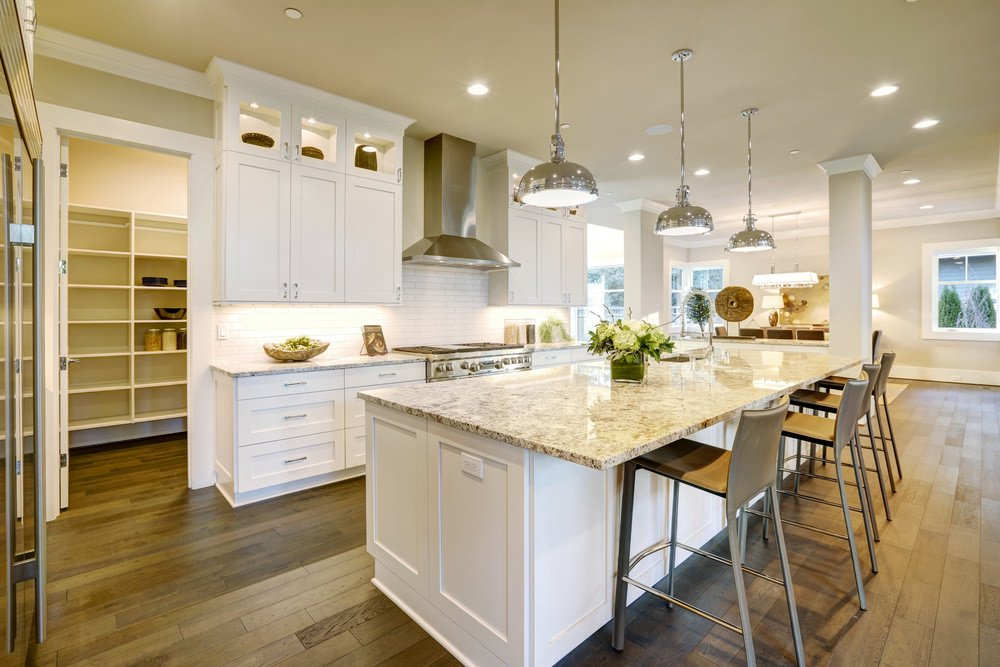 A spacious kitchen with a large marble top island with a breakfast bar and is lighted by pendant lights.