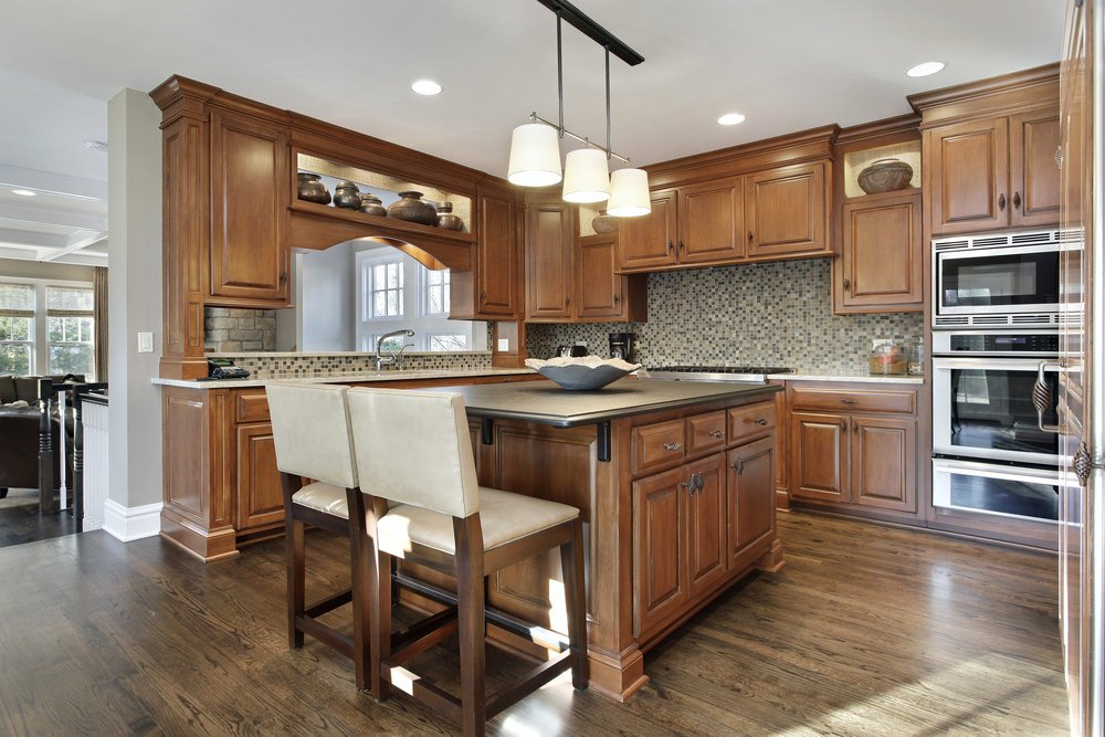 U-shaped kitchen with brown cabinetry and kitchen counters, along with a brown center island with a breakfast bar.