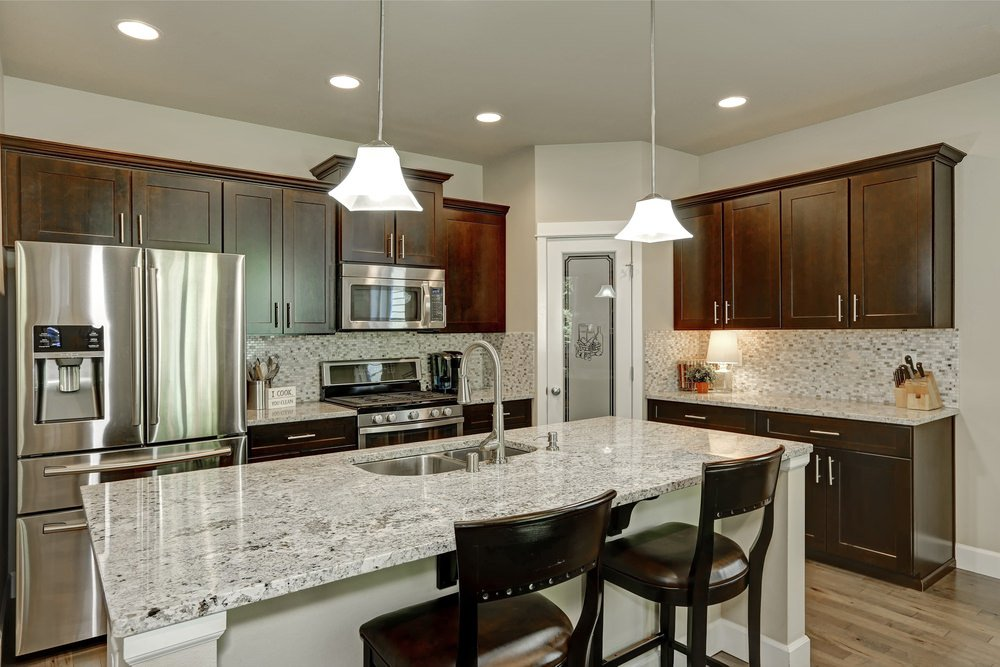 A close up look at this kitchen's marble top island with a breakfast bar lighted by modish pendant lights.