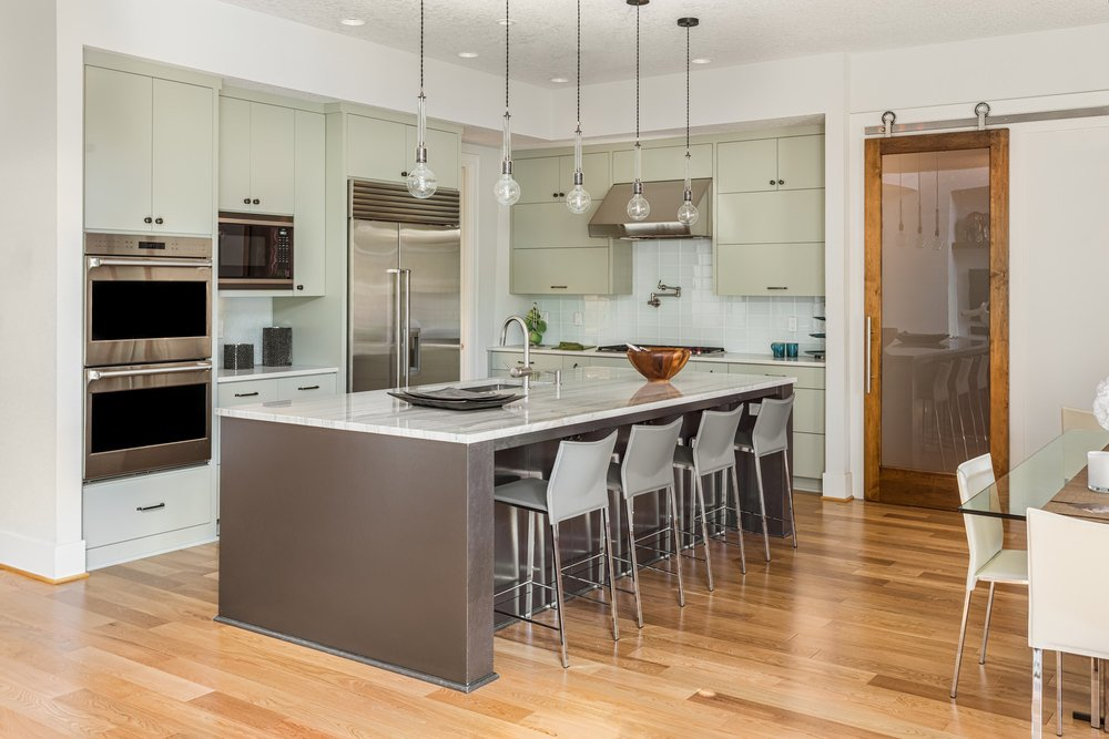 L-shaped dine-in kitchen with a large island with a breakfast bar lighted by pendant lights along with a glass top dining table set.
