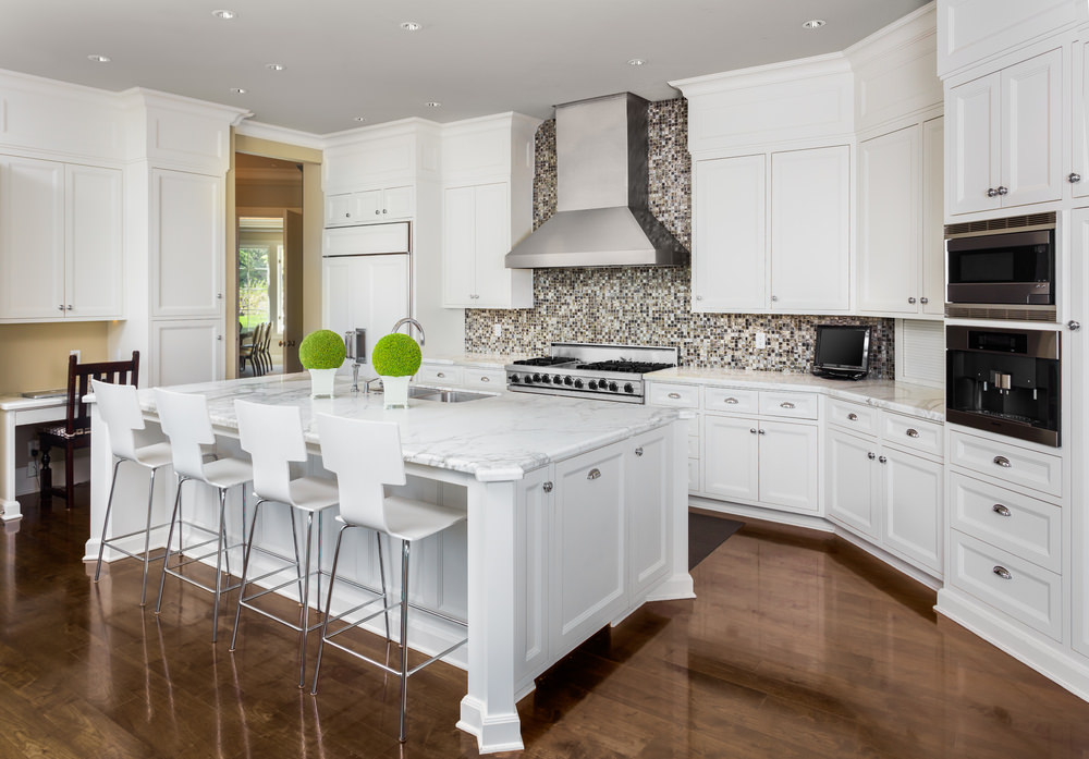 This kitchen offers a large white center island and white kitchen counters with marble countertops. There's a built-in desk on the side as well. This kitchen also boasts a stylish backsplash.