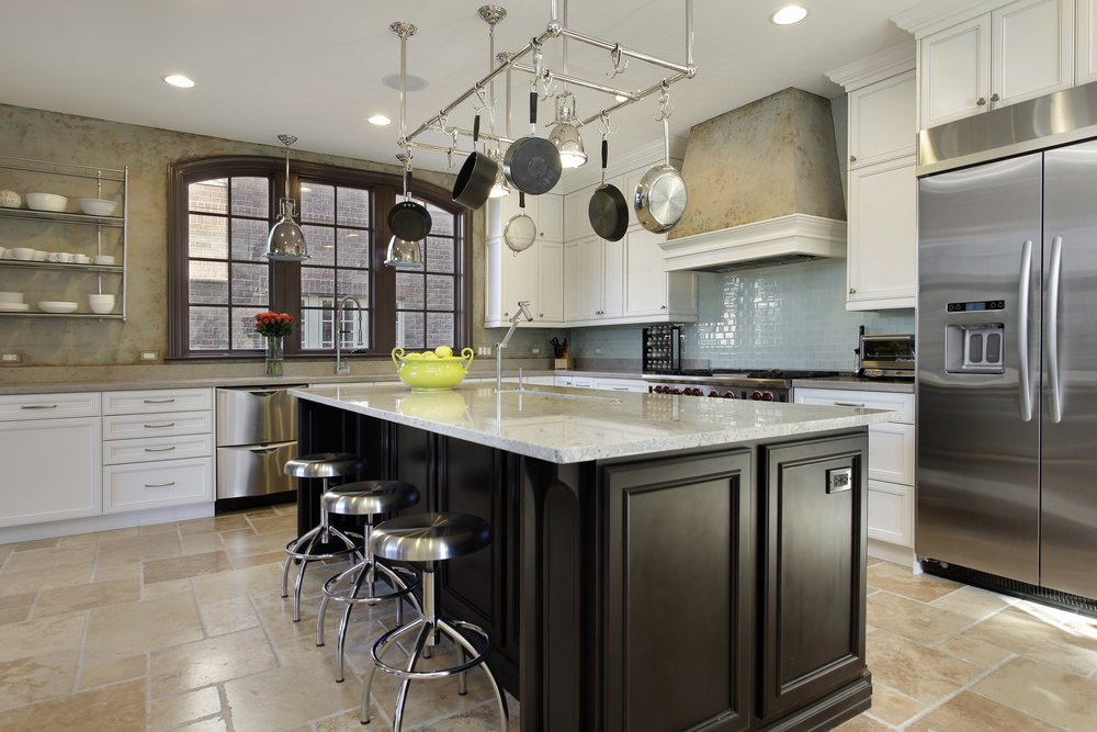 A focused shot at this kitchen's large marble top island with a breakfast bar featuring stainless steel bar stools.