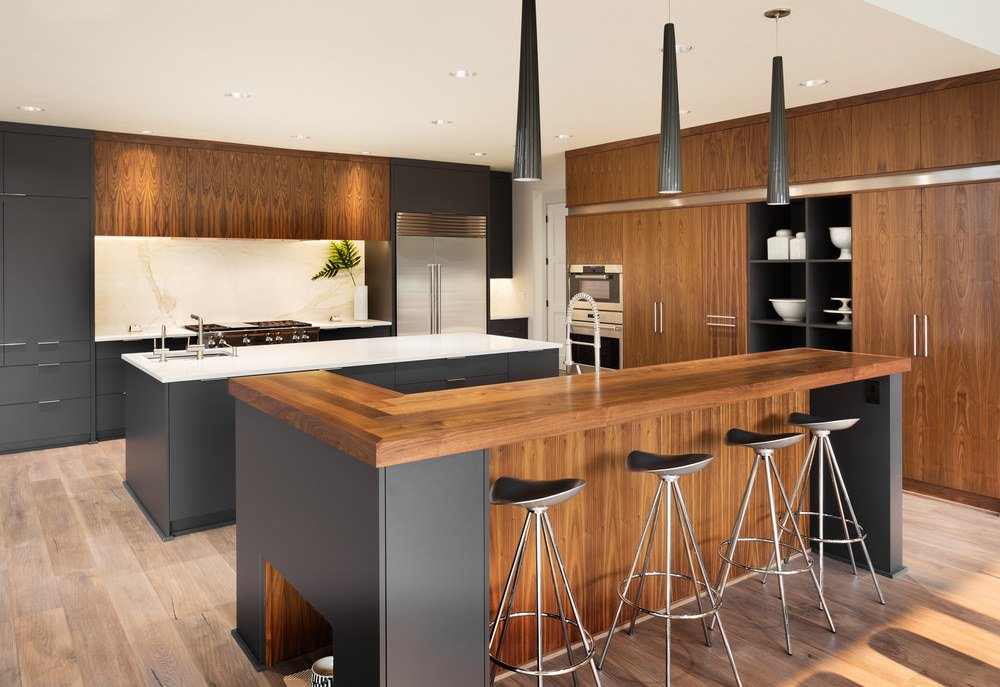 A stylish kitchen with a brown and black color scheme. It features two islands, one serving as a breakfast bar counter lighted by stylish pendant lights.