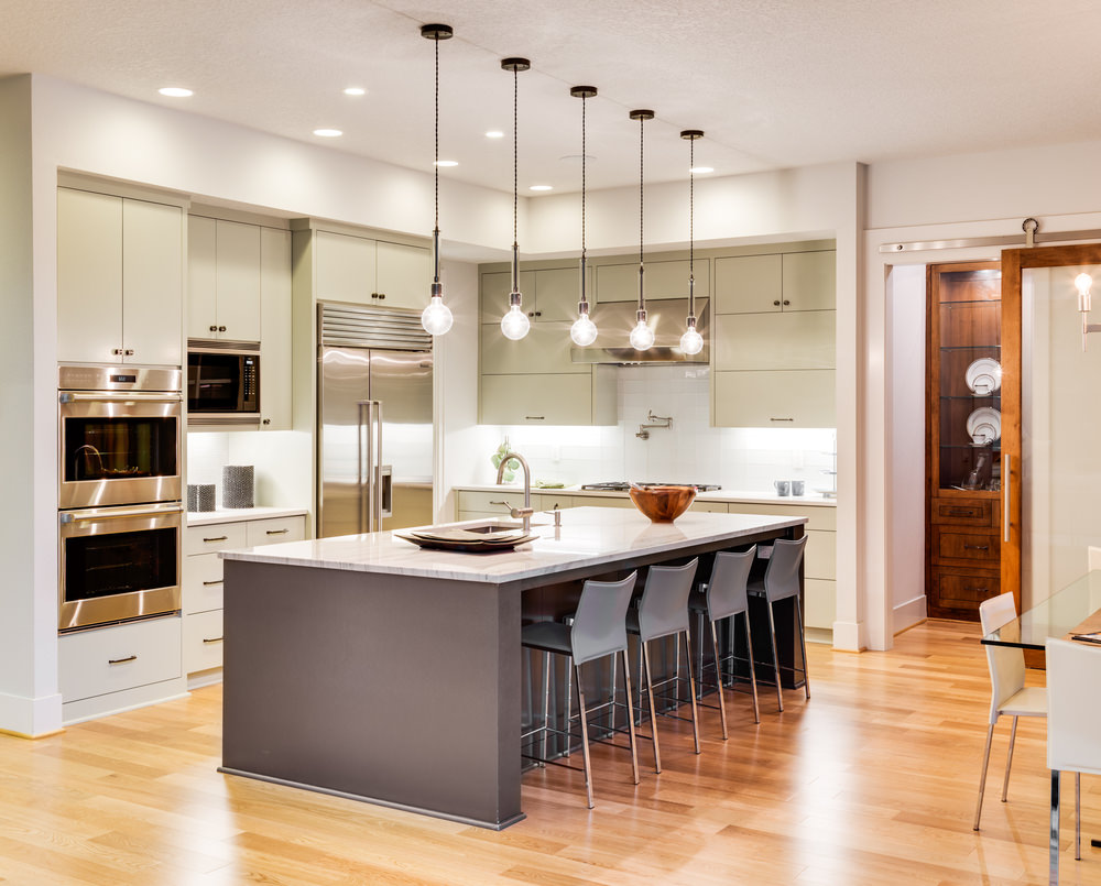 Small L-shaped modern kitchen with a large island featuring a marble countertop and has space for a breakfast bar, lighted by pendant lights.