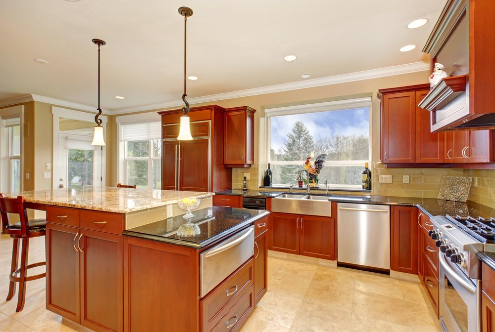 A kitchen with a breakfast bar island and kitchen counters, along with brown cabinetry. The area features brown walls and beige tiles flooring.