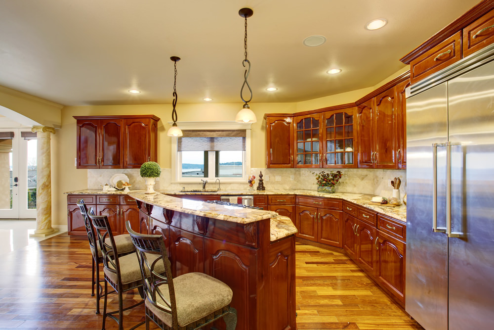 This kitchen boasts yellow walls and hardwood floors. It offers brown cabinetry and kitchen counters, along with a breakfast bar island lighted by pendant lights.