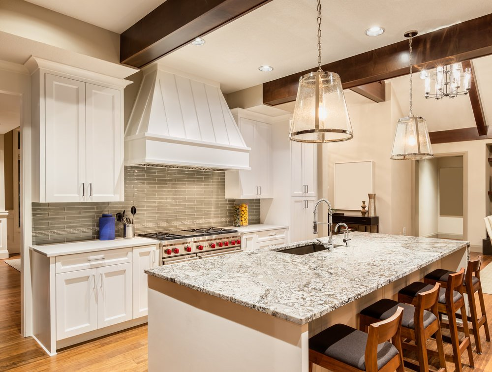 Single wall kitchen area with white kitchen counters and cabinetry, along with an island boasting a marble countertop and has a breakfast bar, lighted by pendant lights.