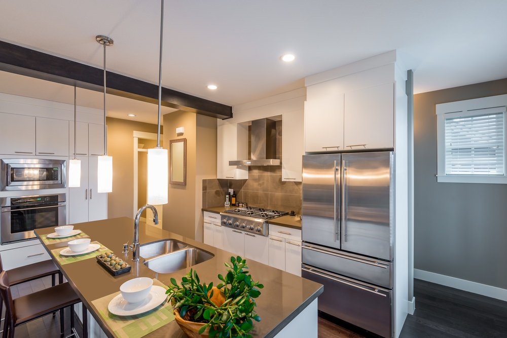 A small kitchen area with an island offering space for a breakfast bar, lighted by attractive pendant lights.