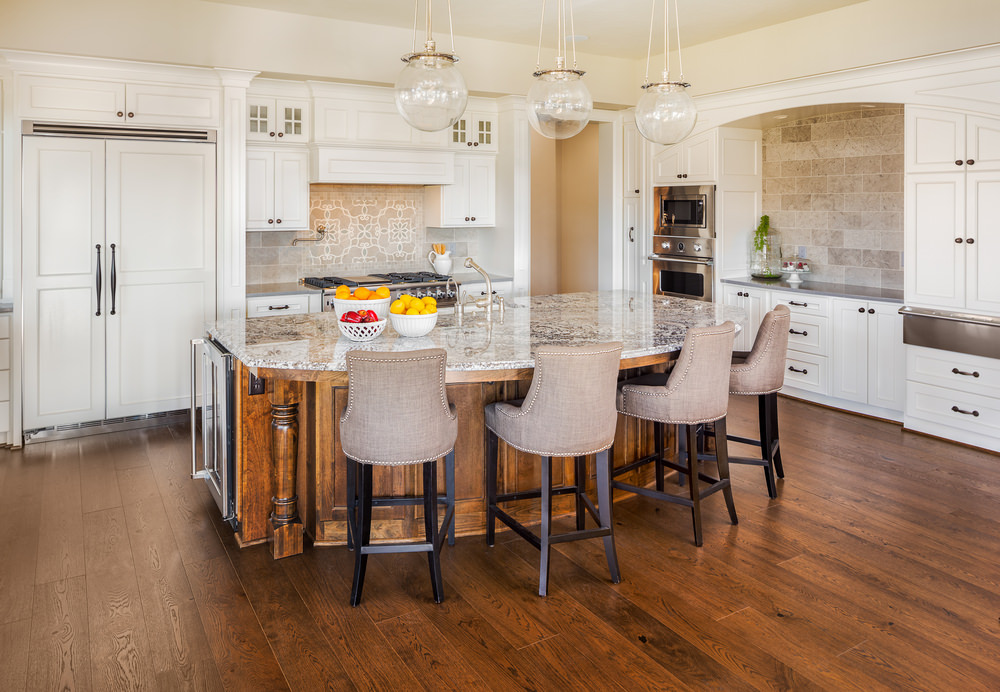 A focused look at this kitchen's custom island with a gorgeous marble countertop featuring space for a breakfast bar, lighted by pendant lights.