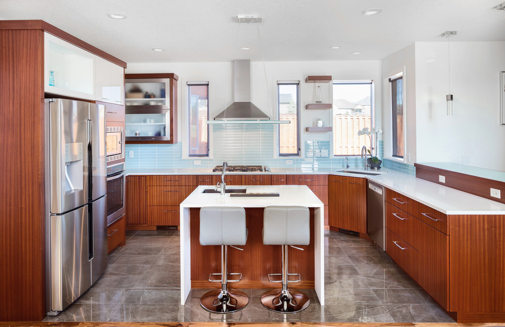 A look at this kitchen with gorgeous gray tiles flooring, white walls and a white ceiling. It offers stylish brown kitchen counter and a square center island with a white countertop.