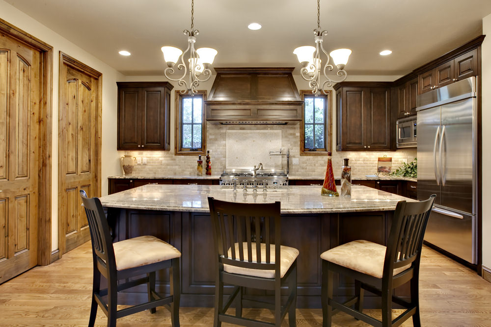 Small kitchen area featuring hardwood flooring, brown kitchen counter and cabinetry, along with an island with a breakfast bar, lighted by charming chandeliers.