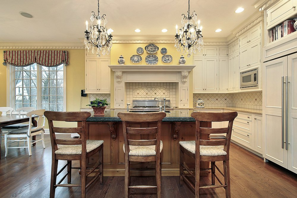 A dine-in kitchen with yellow walls and hardwood floors. It offers a dining table set on the side and an island with a granite countertop and a breakfast bar lighted by gorgeous chandeliers.