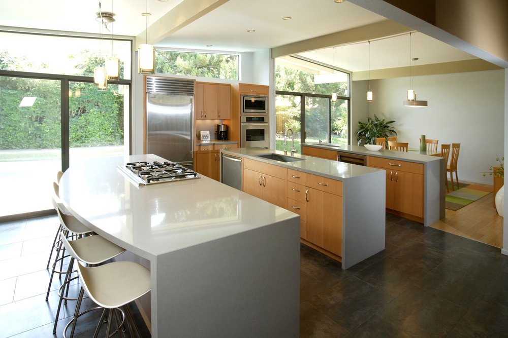 Modern kitchen featuring two kitchen counters and a white island with space for a breakfast bar lighted by charming pendant lights.