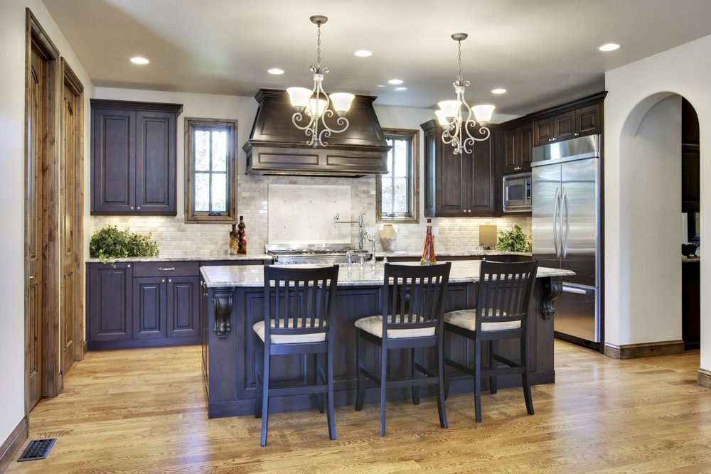 This kitchen features brown kitchen counters and cabinetry, along with a matching island with a breakfast bar, lighted by gorgeous chandeliers.