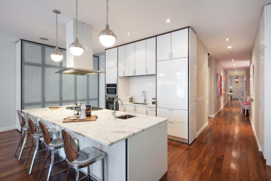 Small modern kitchen area with hardwood floors, white walls and a white ceiling. It offers a large marble island with a breakfast bar lighted by pendant lights.