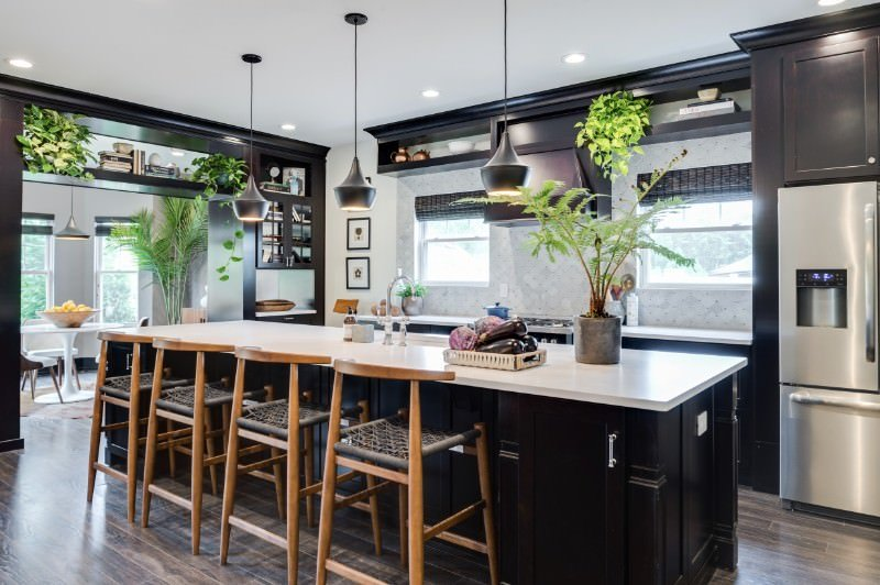Single wall kitchen with a dark brown kitchen counter and a large island with a white countertop and has space for a breakfast bar lighted by stylish pendant lights.