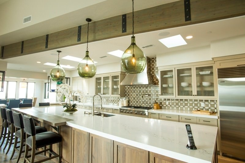 Large single wall kitchen boasting rustic kitchen counter and cabinetry, along with a large island with a white countertop, and has space for a breakfast bar lighted by pendant lights.