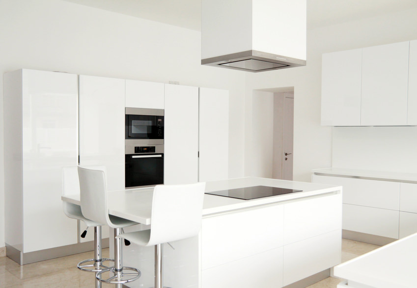 Small white kitchen area with white kitchen counters, white cabinetry and a white island with a white breakfast bar paired with white modern bar seats.