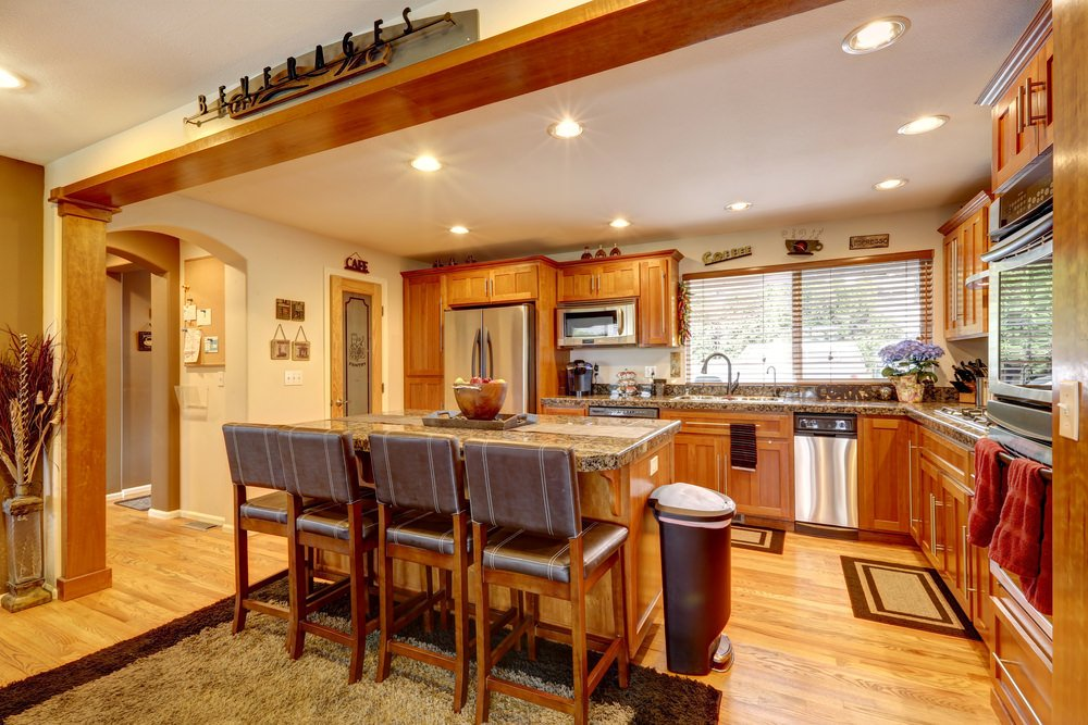 An L-shaped kitchen with brown cabinetry and kitchen counters, along with a center island. The kitchen also has granite countertops and a breakfast bar.