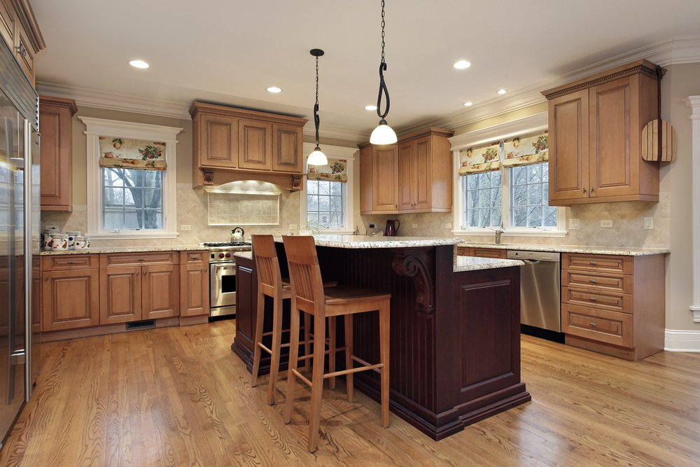 This kitchen has hardwood floors, brown kitchen counters and brown cabinetry, along with a center island featuring a breakfast bar counter.