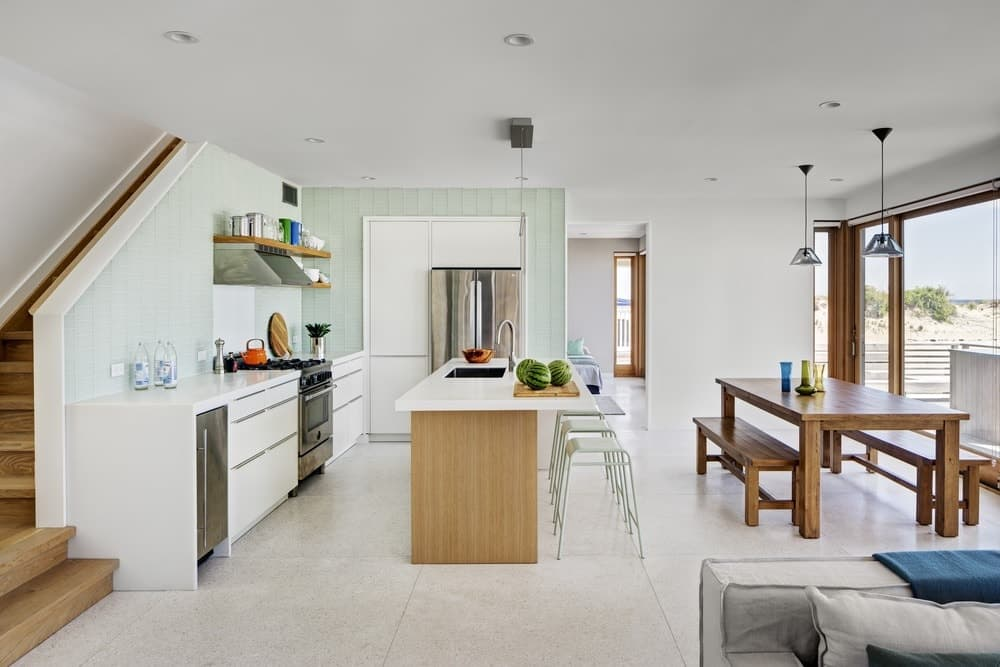 A single wall dine-in kitchen featuring a wooden dining table set and a white countertop breakfast bar, along with a white kitchen counter.