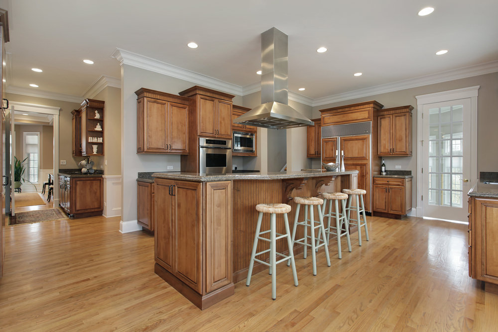 Spacious kitchen area featuring hardwood floors, gray walls and a regular ceiling with recessed lights. It offers brown kitchen counters and cabinetry, along with an island with a breakfast bar.