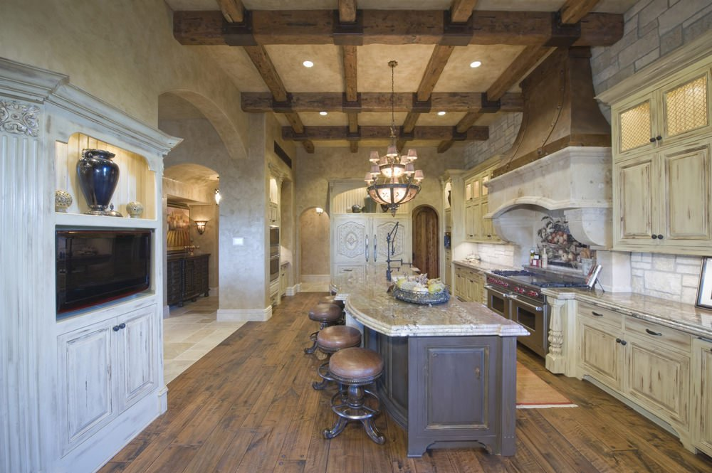 Large Mediterranean kitchen featuring hardwood floors and a tall ceiling with exposed beams. It offers a large island with a breakfast bar and a TV on the wall.