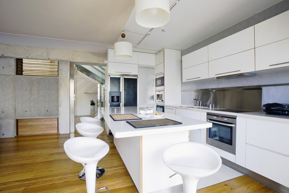 This kitchen offers white kitchen counters and cabinetry along with a white island featuring a breakfast bar paired with white modern bar stools.