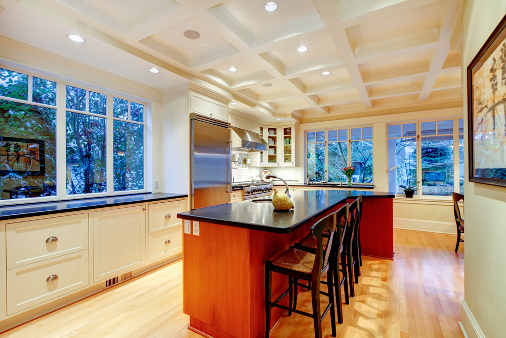 A kitchen with a lovely white coffered ceiling and hardwood flooring. It has black kitchen countertops and a narrow island with a breakfast bar.