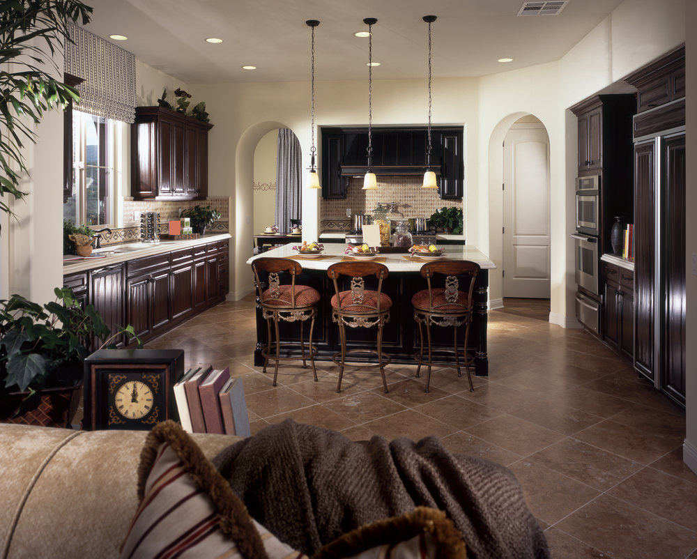 This kitchen features dark brown kitchen counters with white countertops together with a center island with a breakfast bar lighted by pendant lights.