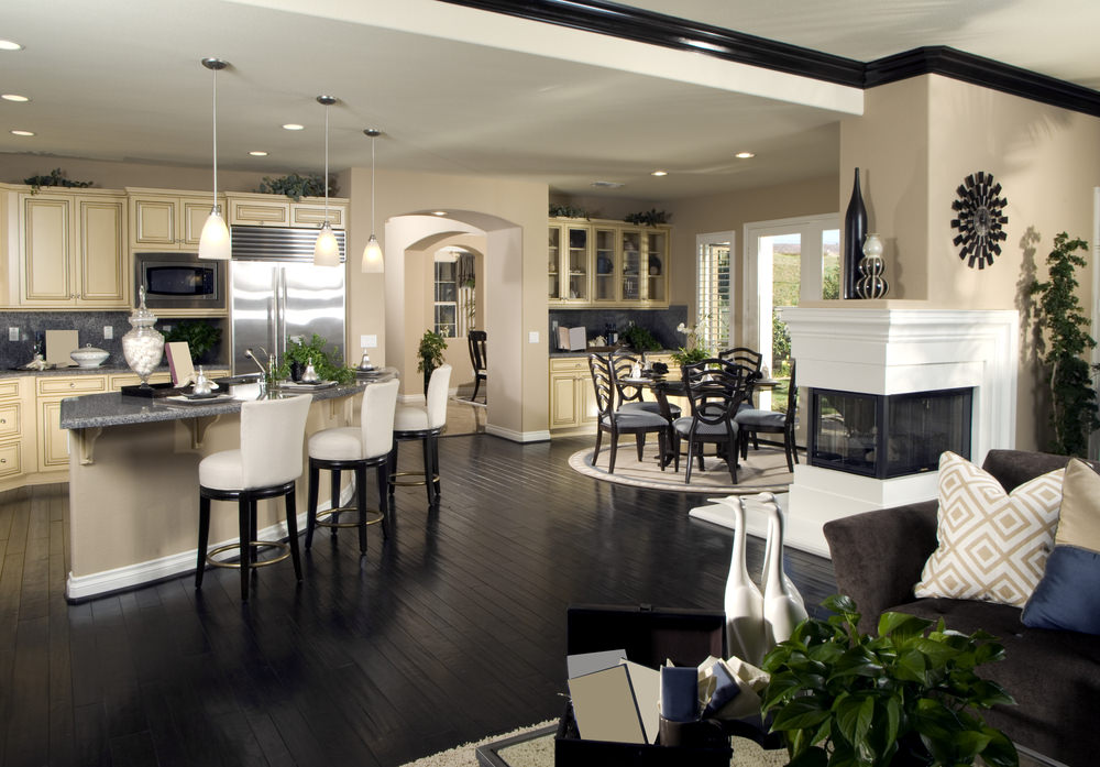 This great room features a comfy living space, a classy dinnig table set and a kitchen with a breakfast bar, together with a fireplace set in the middle.